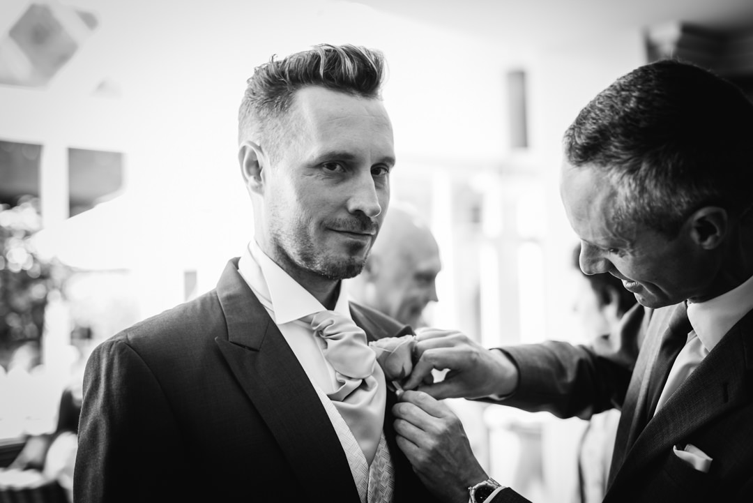 best man attaching button hole to grooms suit lapel at the bull hotel gerrards cross