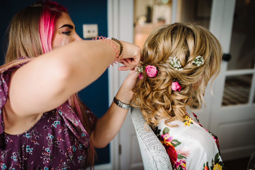 pink flowers being styled into a brides hair