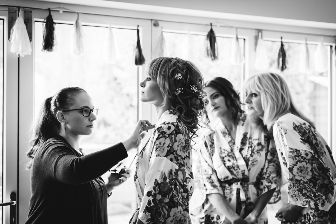 brides mother and sister watch her getting ready