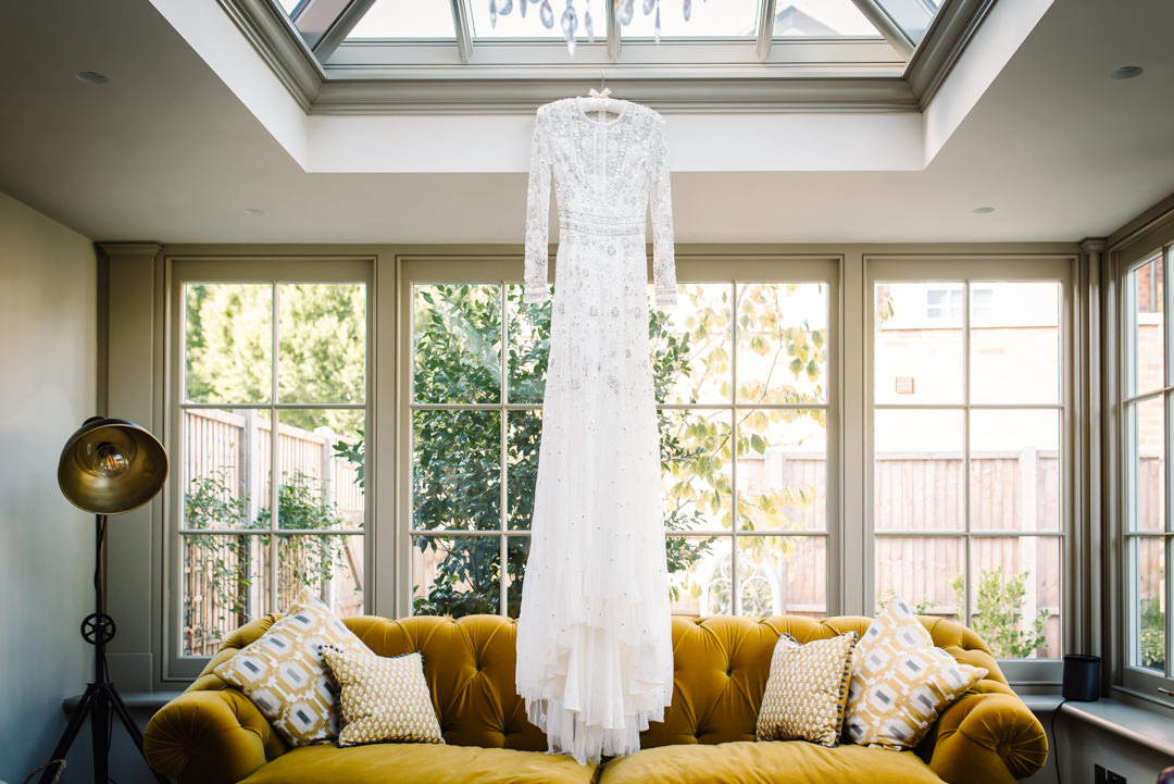 wedding dress by needle and thread hanging ready to be worn