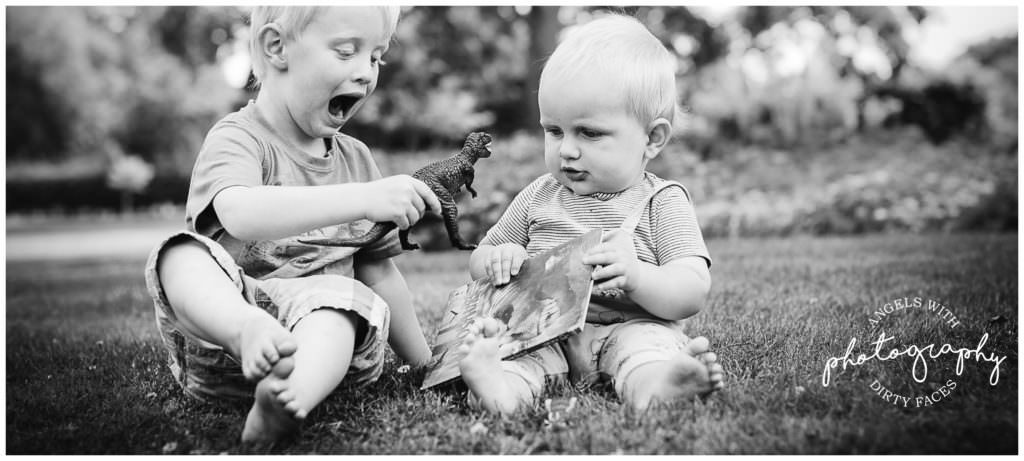 two brothers play with their dinosaurs during their photo shoot