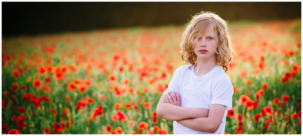 smiling boy in a poppy field at golden hour