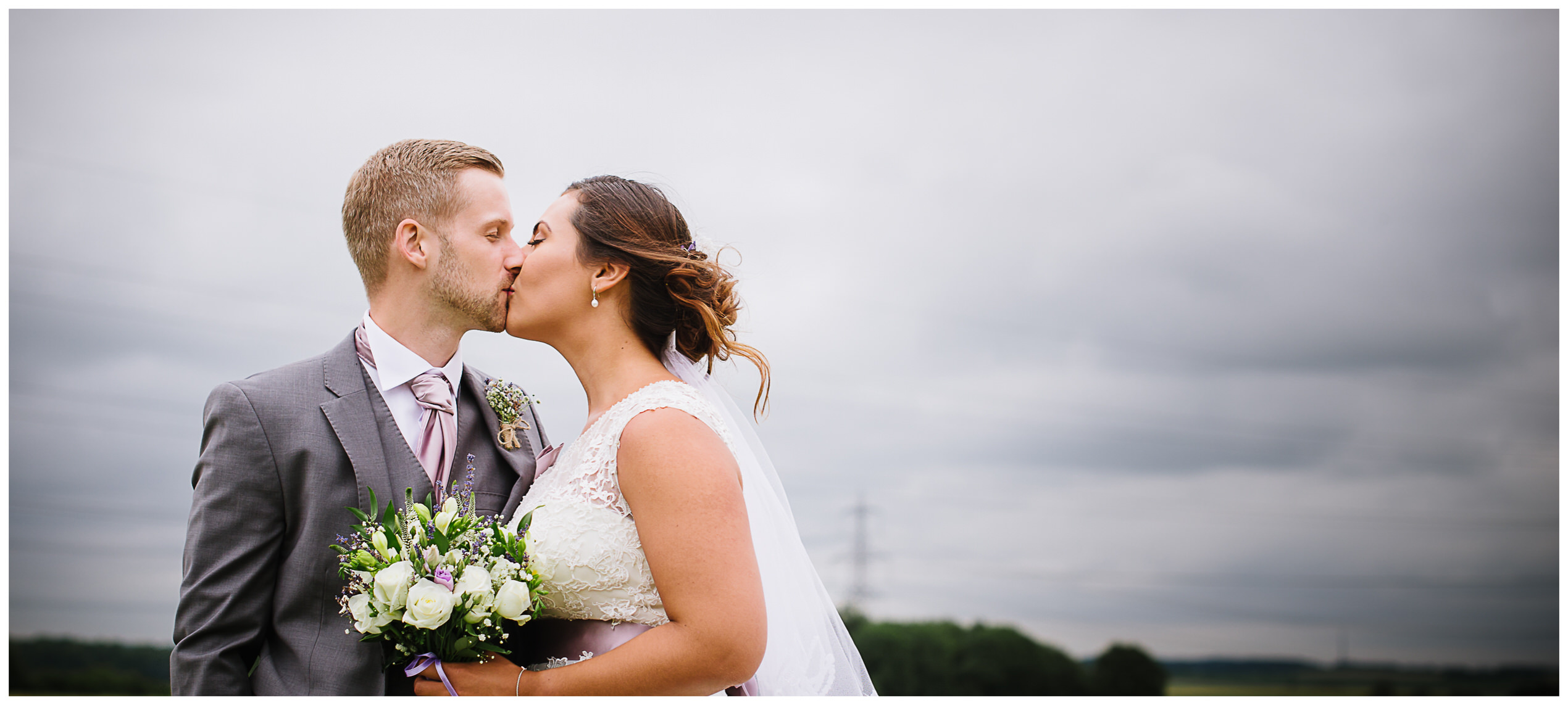 First kiss between bride and groom at their milling barn wedding