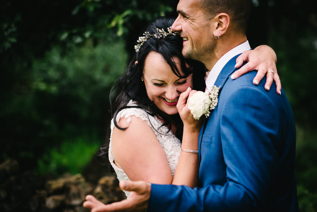 sweetly giggling newly weds pose for their hertfordshire wedding photographer