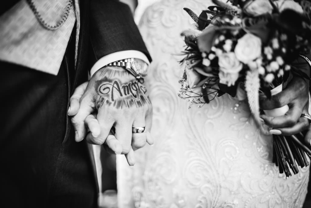 bride and groom hold hands showing his tattoo which spells amore