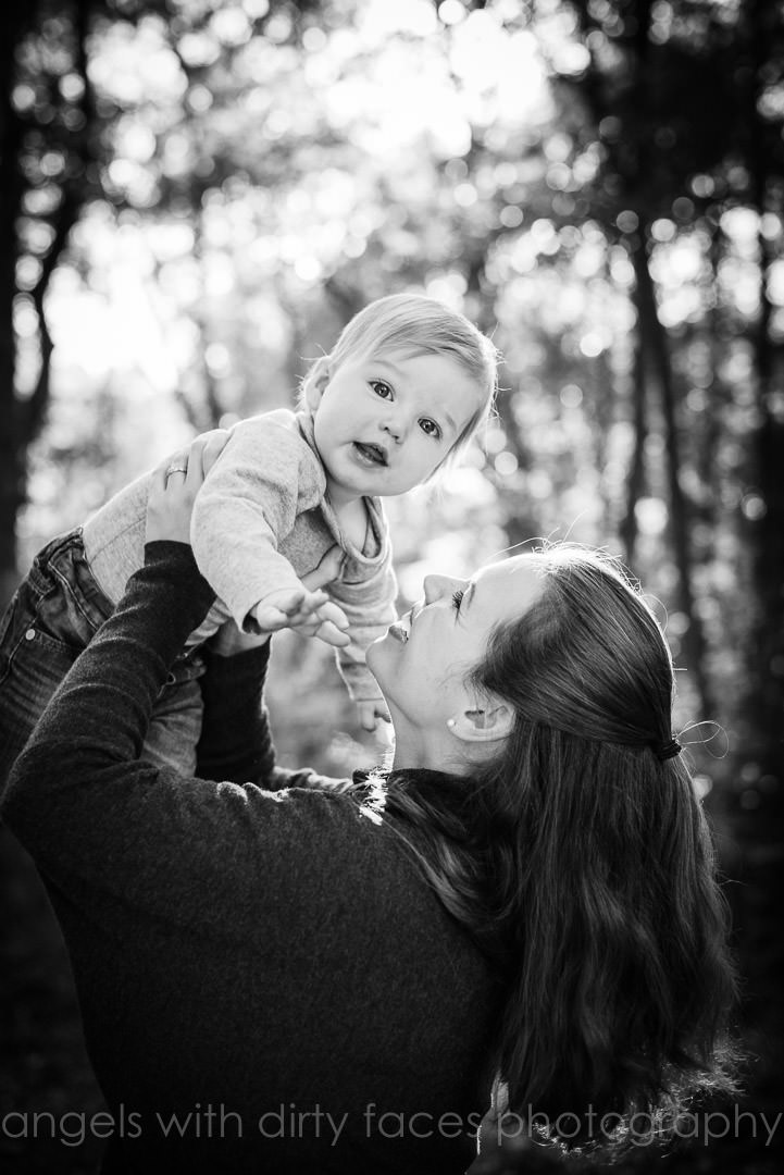 mother throwing baby in air on an autumn photo shoot