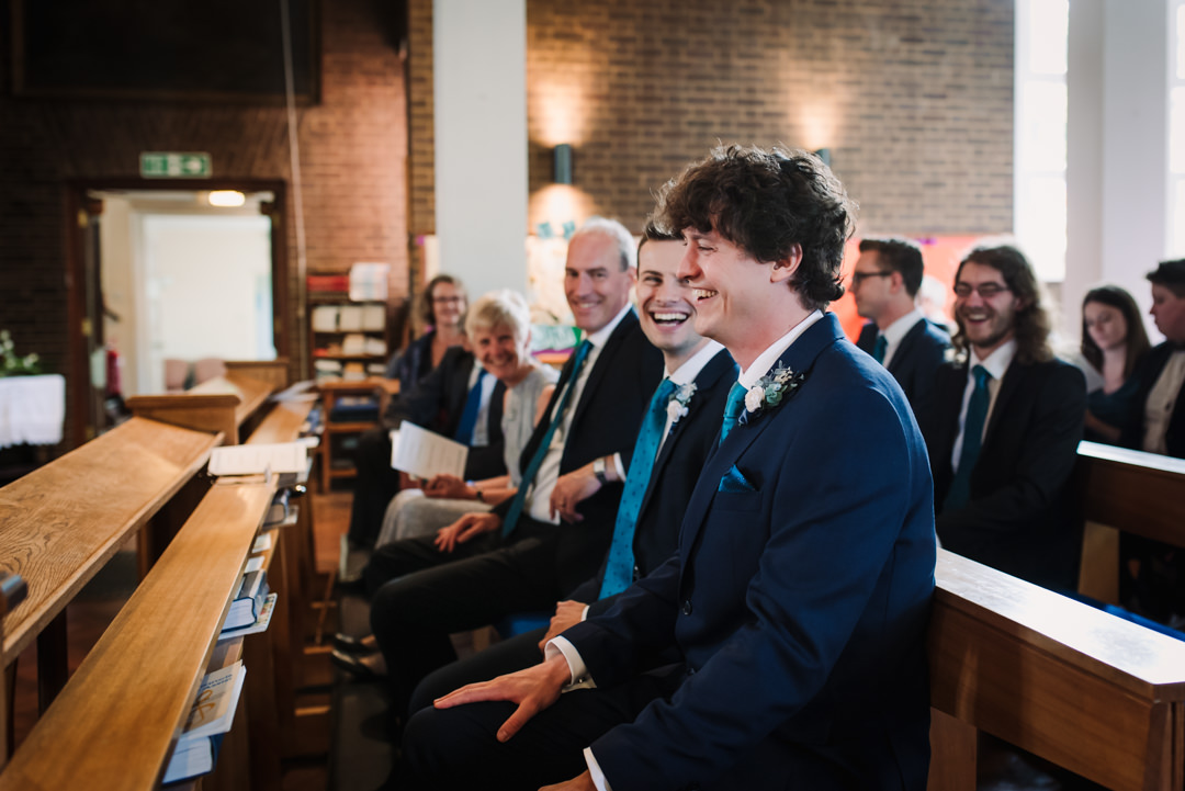 best man and groom laugh together as they wait for the welwyn garden city bride