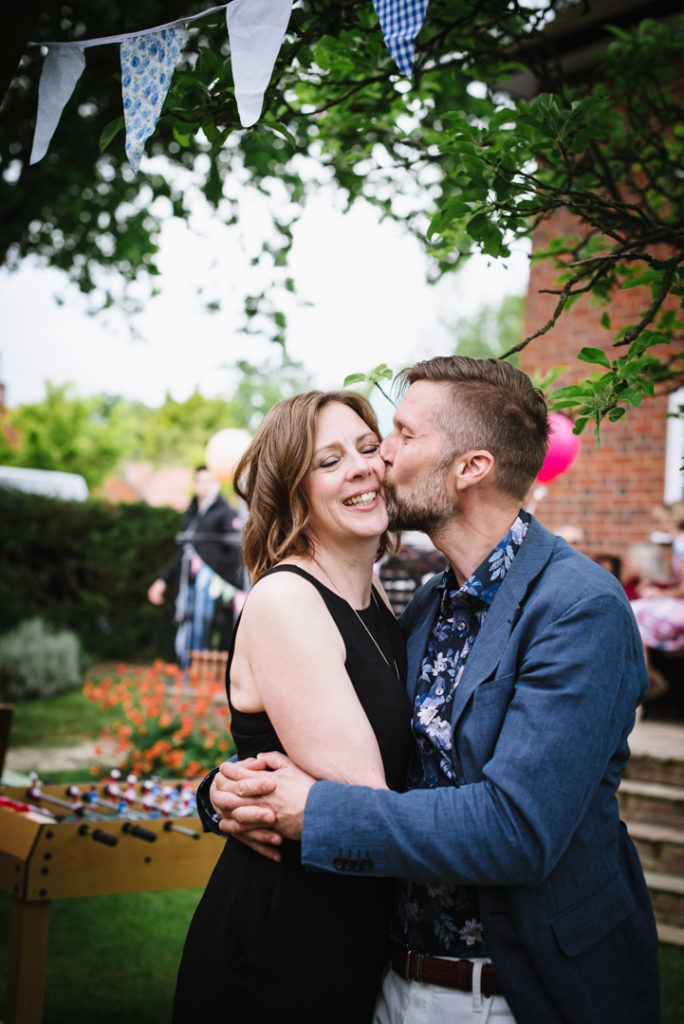 couple at a party kiss for the hertfordshire party photographer