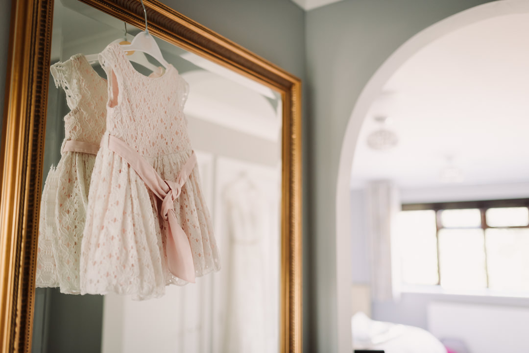 baby bridesmaids dress hangs on a mirror ready to put on