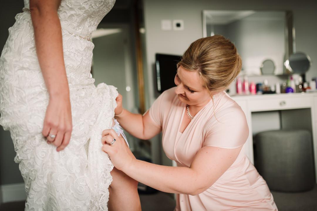 bridesmaid adjusts brides garter before her harpenden wedding