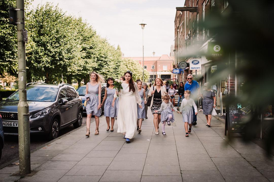 brides walks with her wedding party through welwyn garden city to the church