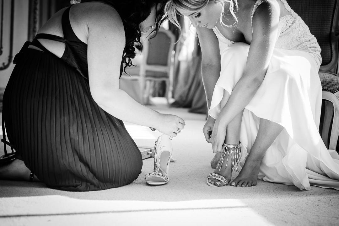 Chief bridesmaid help bride into her wedding shoes