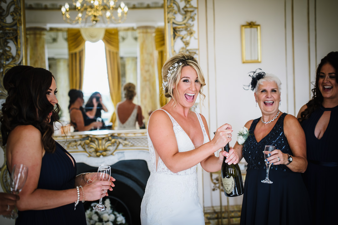 Gosfiled hall wedding photographer documents Bride and her bridesmaids enjoying a glass of champagne before the wedding ceremony.
