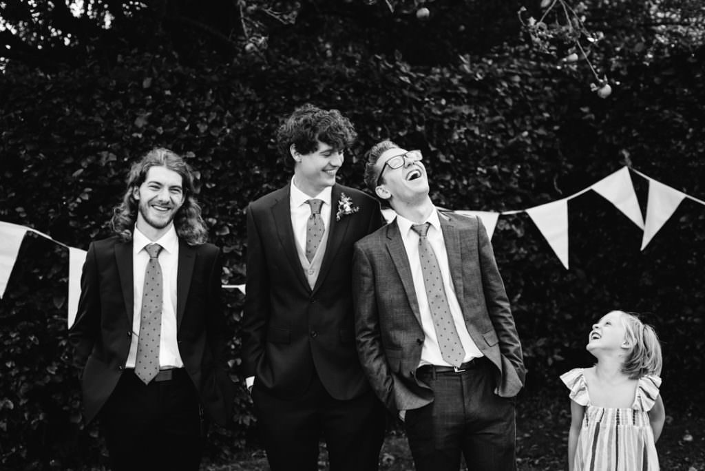 groomsmen laughing at a little kids joke