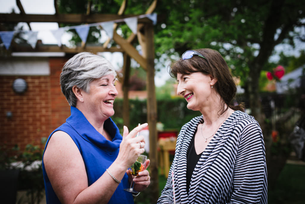 friends laugh together in the garden at hertfordshire party