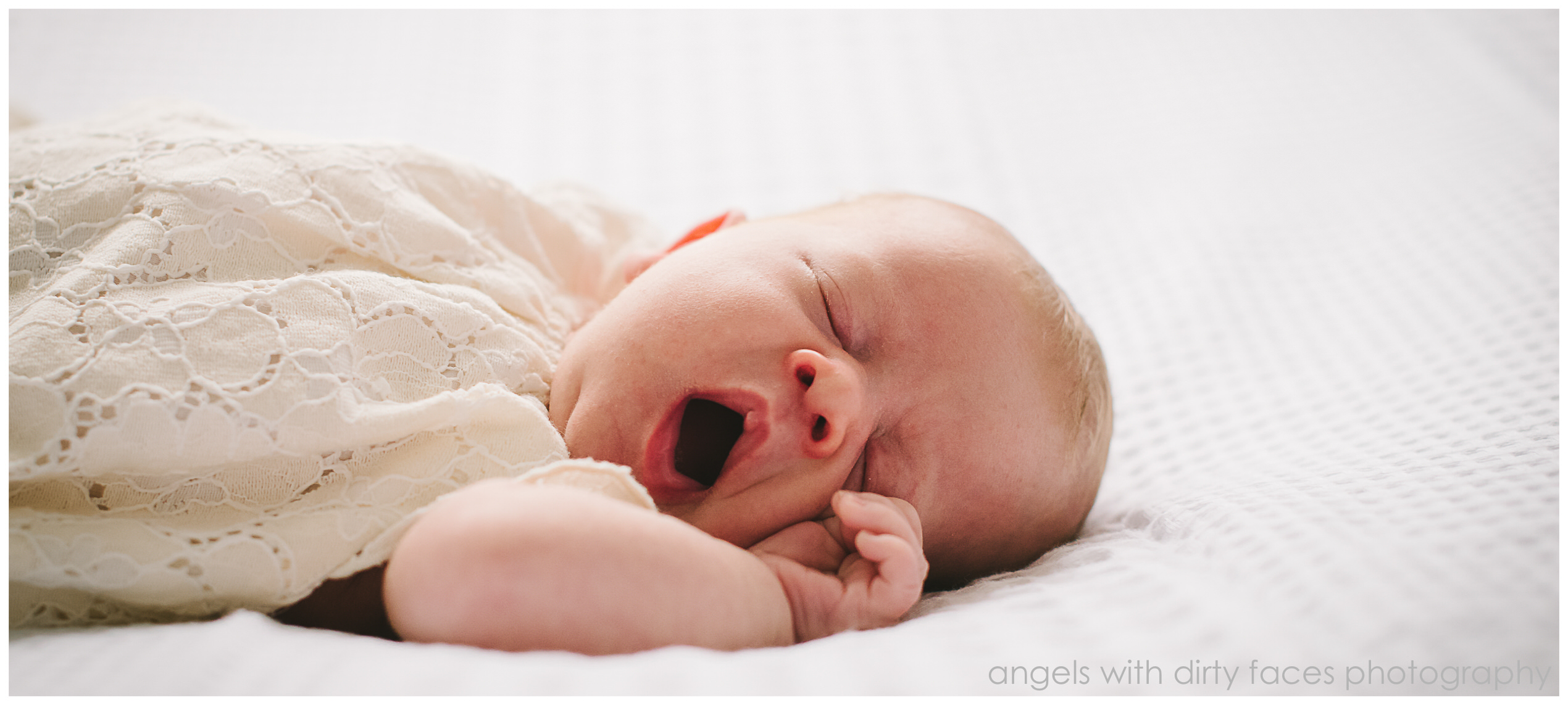 Tiny newborn baby yawns during her photography session
