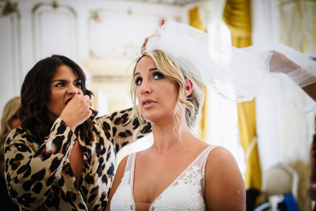 Bridal party help with last minute veil adjustments at Gosfiled Hall wedding in Essex