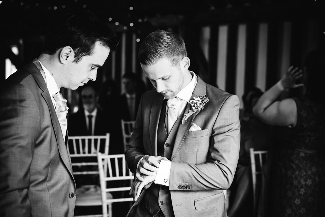 groom nervously looks at his watch at his hertfordshire wedding
