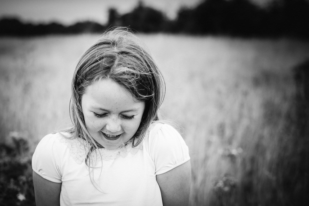 young girl giggles shyly as she stands for her hertfordshire photo shoot featuring in hertfordshire child and family photographer portfolio 2019