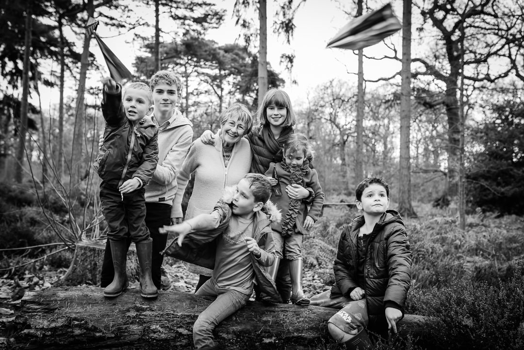 a grandmother plays paper airplanes with her grandchildren whilst on their hertfordshire child and family photo shoot