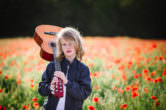 young boy holding his guitar in a sea of poppies